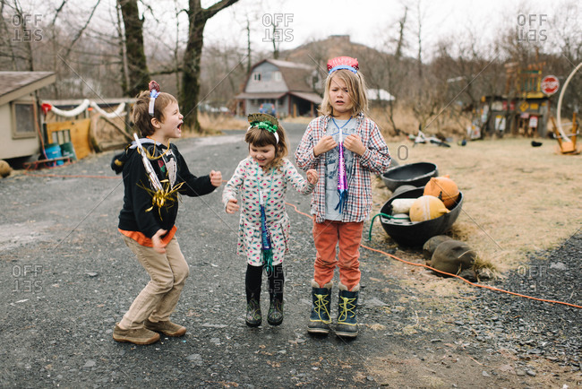 Three children play outdoors with New Year\'s party gear