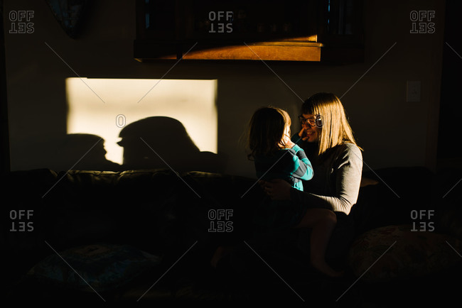 Woman holding toddler girl on her lap on sofa