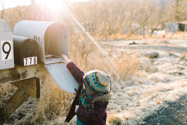 Toddler girl reaching up to get mail from rural mailbox