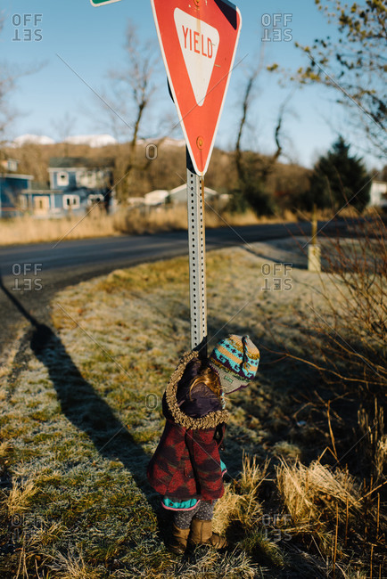Toddler girl playing in frosty grass next to Yield sign