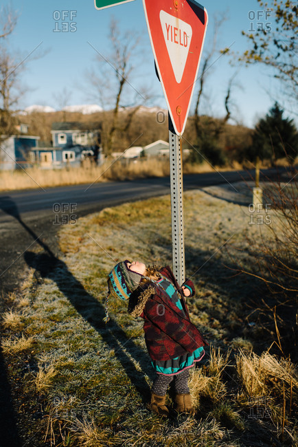 Toddler girl looking up at traffic sign