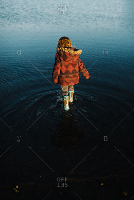 Back view of toddler girl walking in water with rubber boots