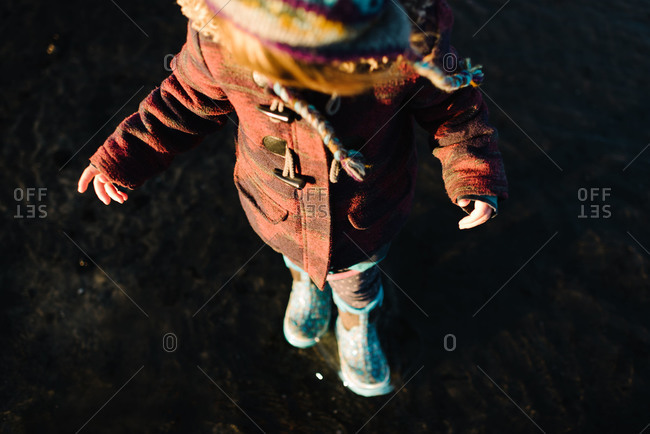 Overhead view of toddler girl in rubber boots walking in water