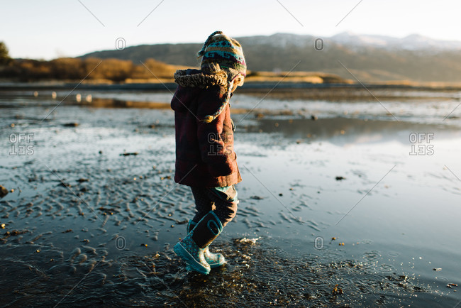 Girl walking on mudflat in rubber boots