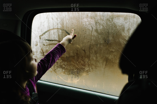 Girl drawing in condensation of car window
