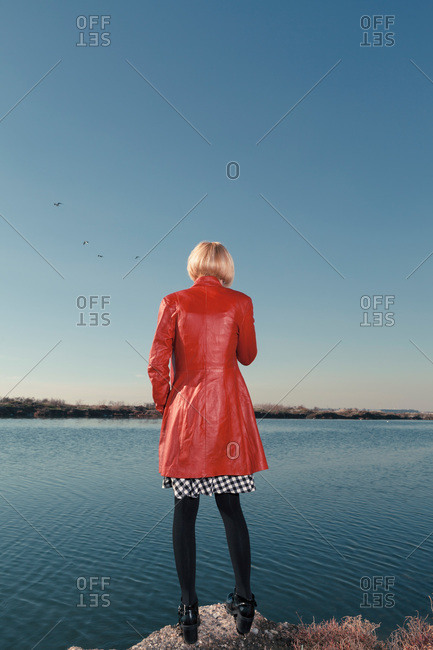 Back view of a woman in red coat standing on rock at shore