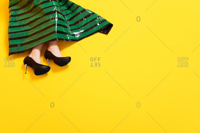 Feet and skirt of woman in dress made of black plastic and green sticky tape
