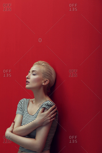 Woman in striped shirt stands against red wall with eyes closed