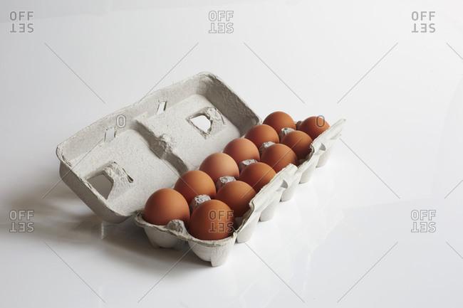 One dozen brown eggs in a carton