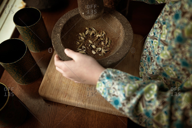 Girl grinding cardamom seeds with mortar and pestle