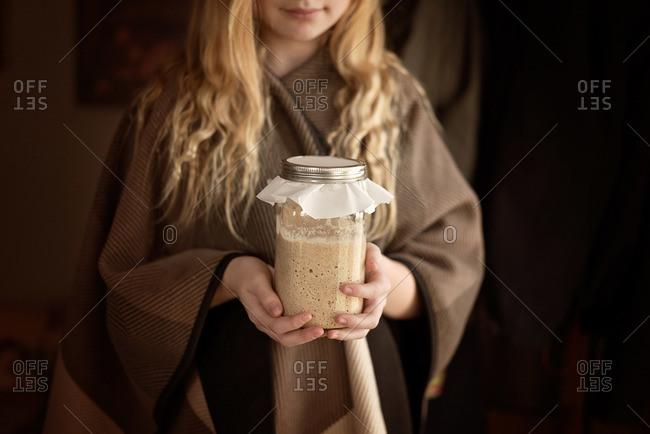 Girl holding a jar of sourdough starter
