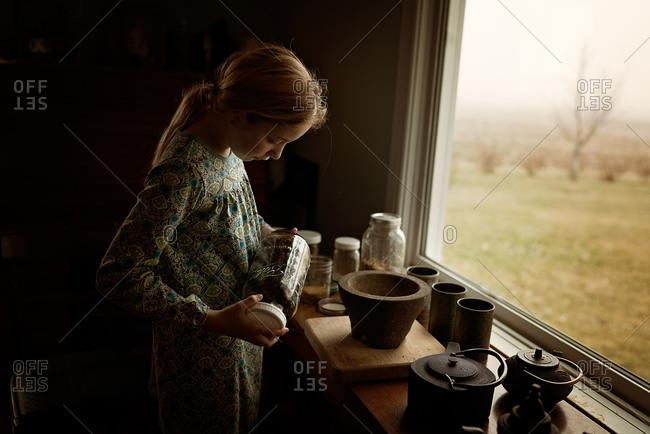 Girl looking at contents of a mason jar
