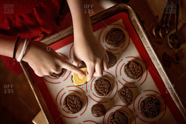 Girl placing cookies on a non-stick mat