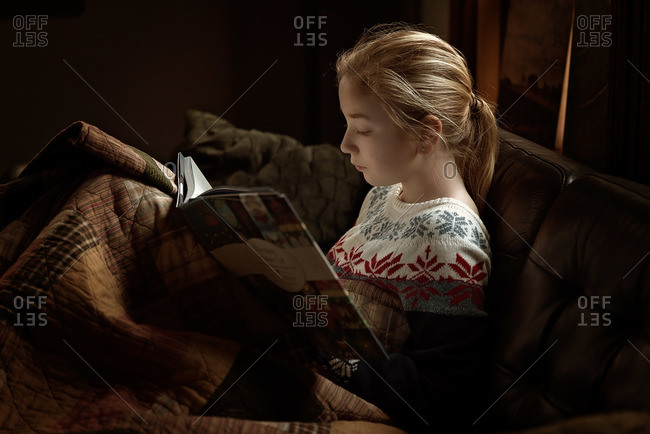 Girl curled up on a couch reading a book