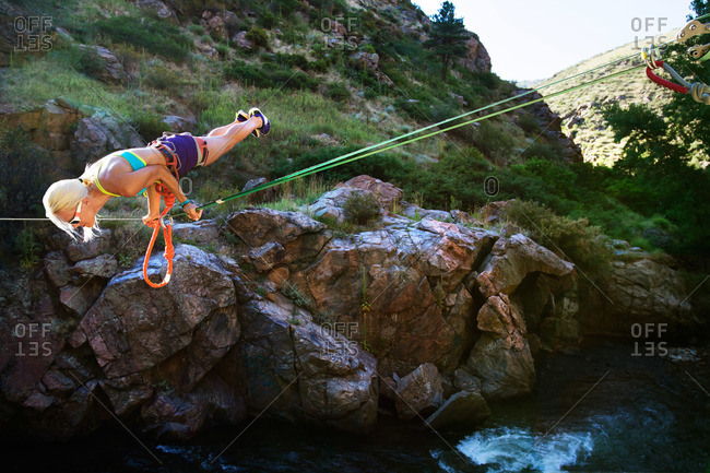 Athletic woman doing tricks while crossing a river with a rope