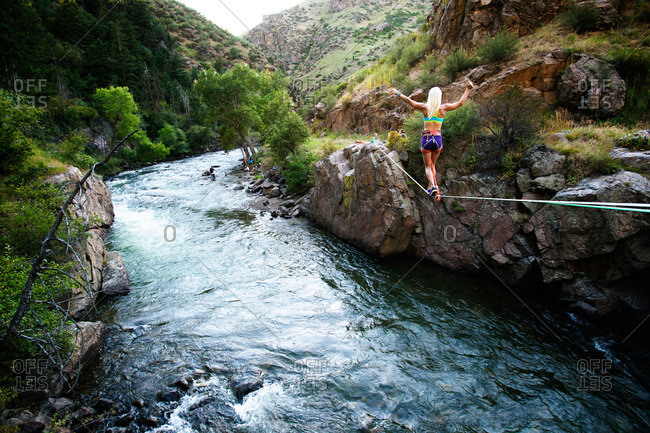 Woman walking on a tightrope over a river