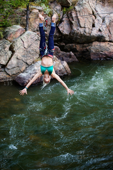 Athletic woman doing tricks from a rope over a river