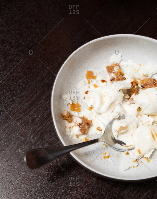 Bowl of ice cream with crumbled cookies and spoon