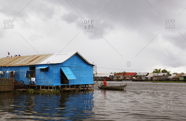 Man paddling boat past house on river
