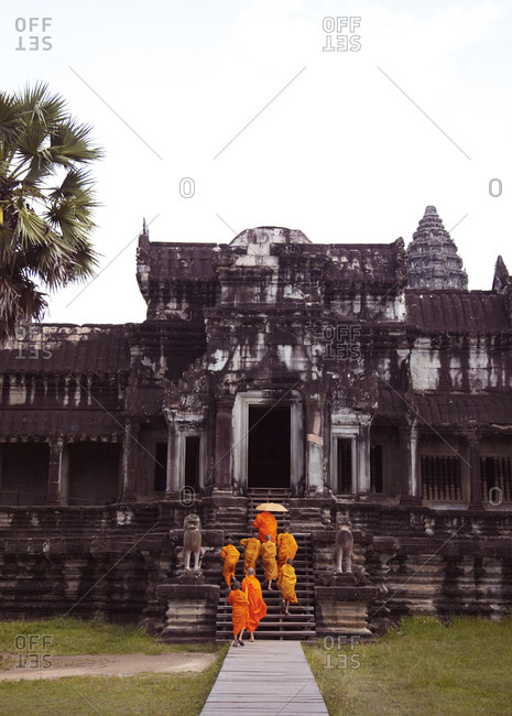 Monks in orange robes climb steps of temple in Cambodia