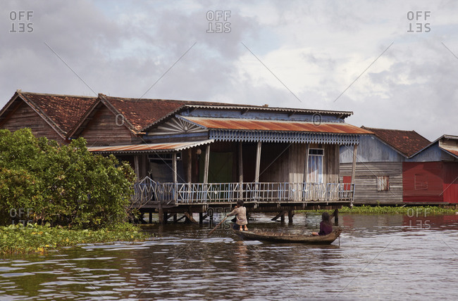 Man and woman on boat paddling near river homes