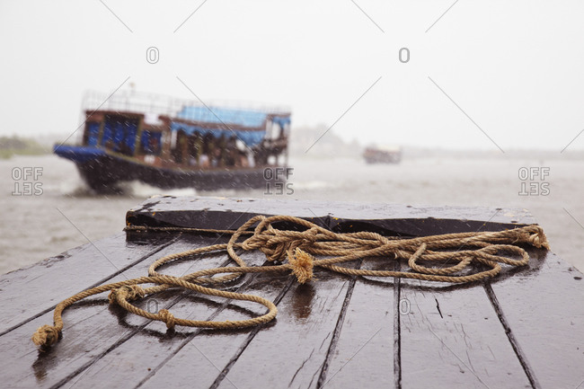 Close up of rope on dock with riverboat in distance