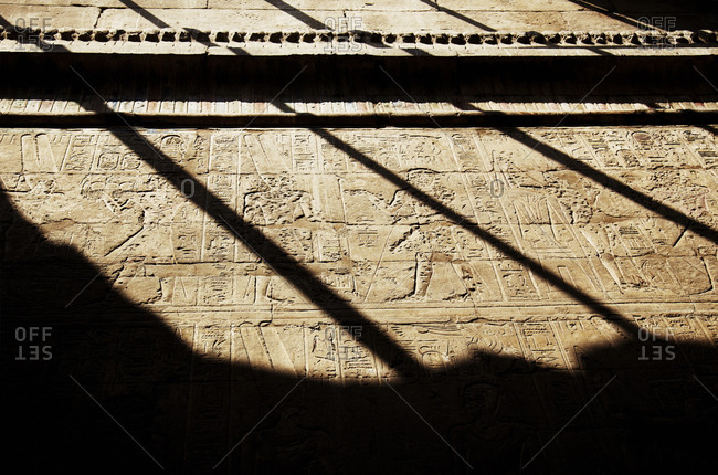 Carved stone walls with hieroglyphics and figures at temple in Egypt