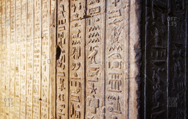 Close up of hieroglyphics in relief on wall in Egypt
