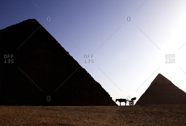 Horse cart silhouetted between two pyramids in Egypt