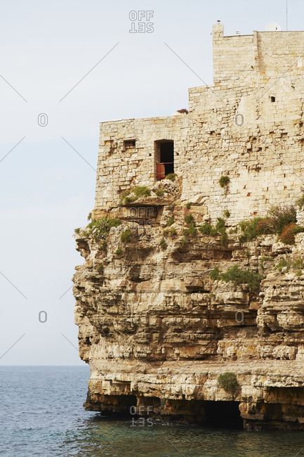 Window in building atop stone cliff in Italy