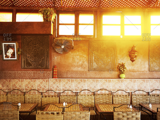 Marrakech, Morocco - January 10, 2015: Tables and chairs along wall below windows in cafe