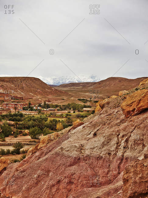 Buildings in village with snowy mountains in distance in Morocco