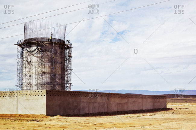 Workers constructing concrete tower behind wall in Morocco