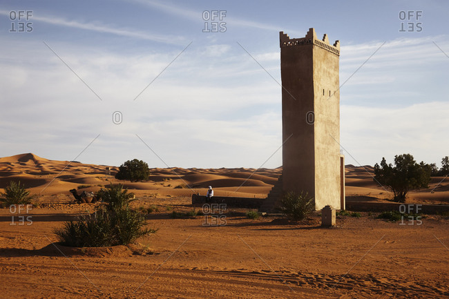 Moroccan man sitting on wall at observation tower with camel nearby