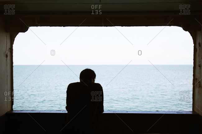 Back view of man looking out window at water, Thailand