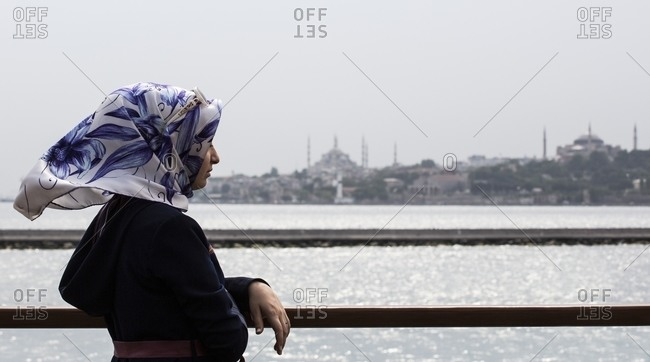 Istanbul, Turkey - June 19, 2014: Woman looking out at the Bosphorus strait