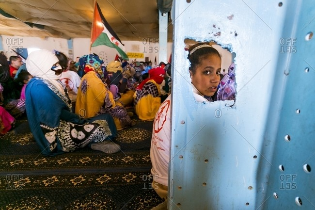Tindouf, Algeria - February 27, 2015: A young girl sitting on the floor during a meeting in the refugee camp of Dahkla