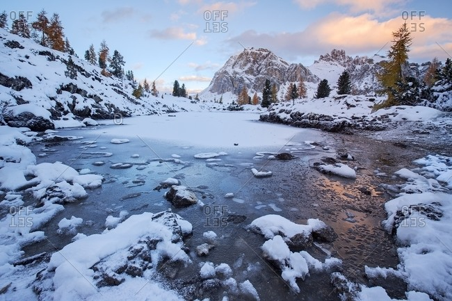 Sunrise on the frozen Lake of Limedes with the peaks of Lagazuoi on background, Belluno, Italy