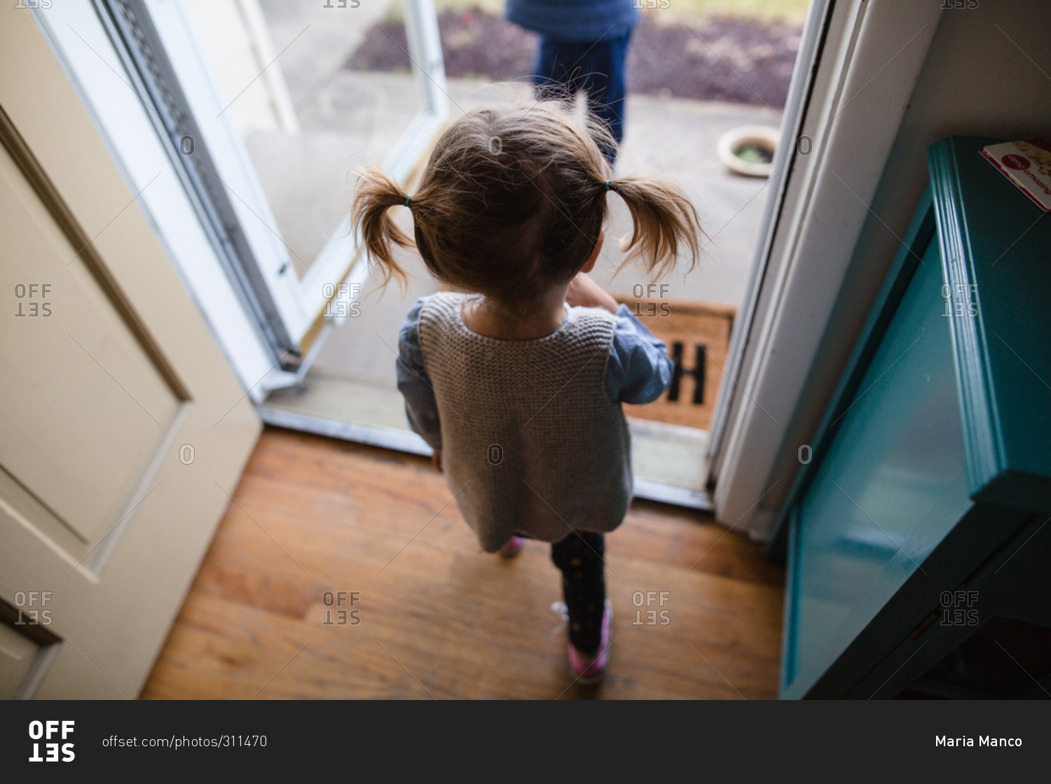 Little girl with pigtails walking out the front door stock photo