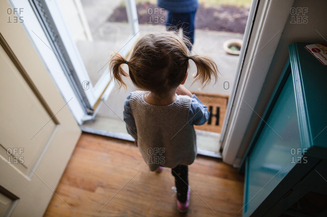 Little girl with pigtails walking out the front door