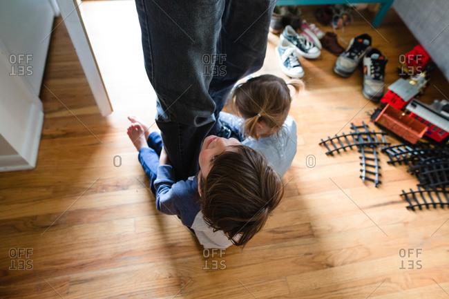 Children clinging to father's feet as he walks in the door