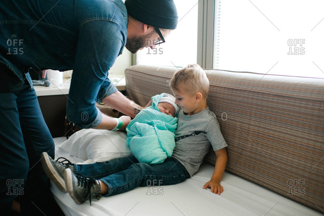 Father introducing newborn baby to brother