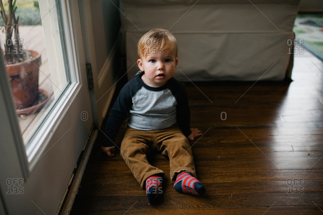 Toddler boy sitting by a patio door