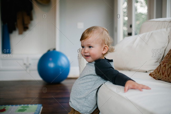 Toddler boy leaning on sofa