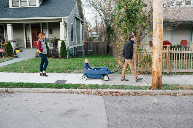 Parents walking with toddler in a wagon
