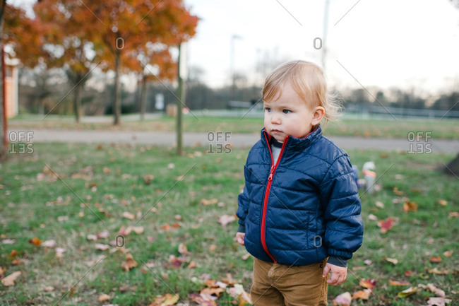 Toddler boy standing outside in the fall