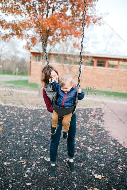 Mother pushing toddler boy on a swing