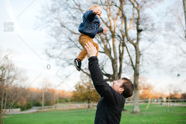 Father throwing toddler boy into the air