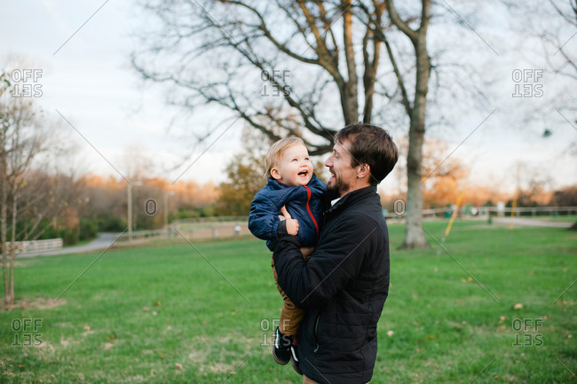 Father lifting toddler son laughing
