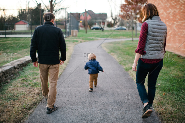 Parents walking in a park with toddler son